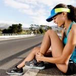 Female athlete sitting on kerb holding her shin