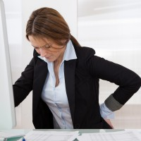 Women sitting at desk suffering with low back pain